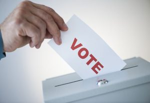"Image of a hand placing a paper with the words ""vote"" on it into a ballot box."
