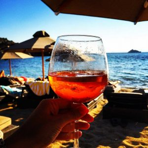 Image of a hand holding an Aperol spritz in front of a beach scene in celebration