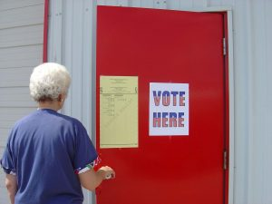 "Image of a person wearing a blue shirt opening a red door. The red door has a sign that says: ""Vote Here"""