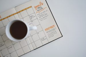 A coffee mug sits atop of an open monthly planner with notes.