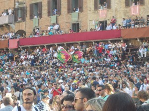 This is a picture of the Piazza del Campo during the Palio, when the parade of the contrade marched in. The flags in the background are from the Drago contrada, the winning contrada of the Palio.